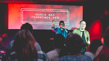 people singing on stage at a worship service