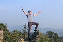 a man standing on a mountaintop with arms raised