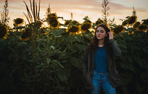 teen girl standing in a field of sunflowers