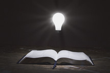 glowing lightbulb and an open Bible