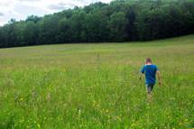 a boy child walking through a field of tall grass