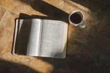 An open Bible lying on a tile floor and coffee mug