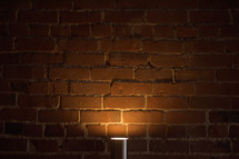 lamp glowing against a brick wall