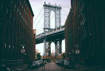 view of the Brooklyn Bridge through an alley