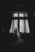 A bride poses in front of a window