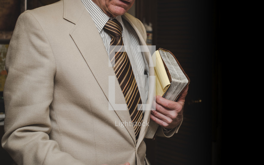 a man in a suit carrying a Bible