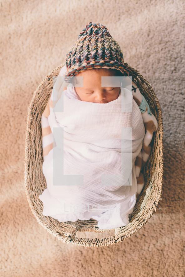 newborn sleeping in a basket