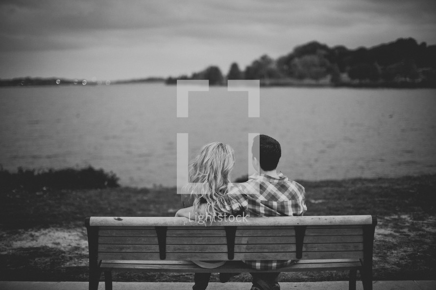 Couple sitting on a park bench by the ocean.