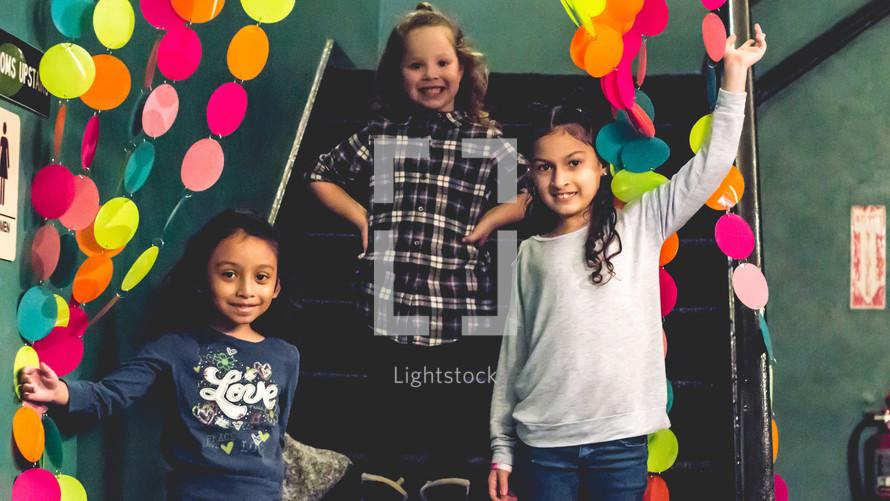 children standing on steps smiling
