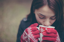 A woman in red gloves drinking hot chocolate from a Christmas cup.