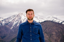 a man standing in front of a snow covered mountain peak