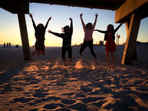 teen girls jumping in the sand under a pier on a beach