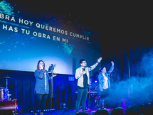 worship leaders performing on stage in front of a projection screen with Spanish lyrics