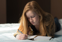 teen girl writing in a journal on a bed