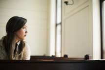 Woman looking out the window while sitting in a church pew.