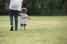 mother and daughter walking holding hands outdoors