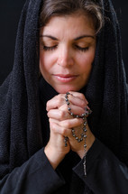 woman in soulful prayer holding a rosary
