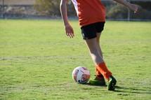 a girl dribbling a soccer ball