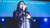 woman holding microphones singing during a worship service
