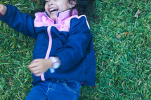 a little girl in a jacket rolling in the grass