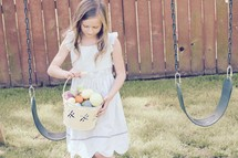 A little girl searching for eggs in a backyard Easter egg hunt