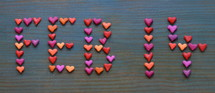 The date FEB 14 for February 14th written with many little colorful clay hearts on cyan wooden background