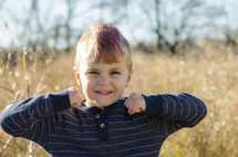 a little boy with a mohawk standing outdoors