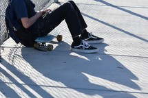 a boy sitting next to his skateboard