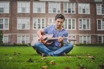 man sitting in grass playing a guitar