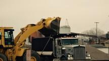 A front loader loading a dump truck