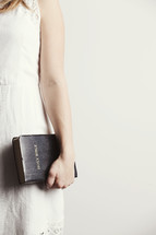 Woman holding a Bible by her side.