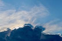 sunlight behind tall clouds