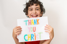"Smiling boy holding a ""Thank You Christ"" written in crayon."