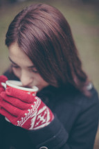 A young woman in red gloves drinks hot chocolate from a Christmas cup.