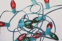 A bundle of red and green Christmas lights on a white background.