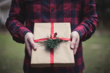 A man holding a gift wrapped in brown paper and red ribbon