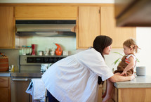 a mother talking to her toddler daughter who is sitting on a kitchen countertop