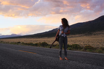 a young woman standing in the middle of a road holding a guitar