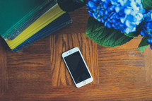 hydrangea flowers, stack of books, and cellphone on a wood table