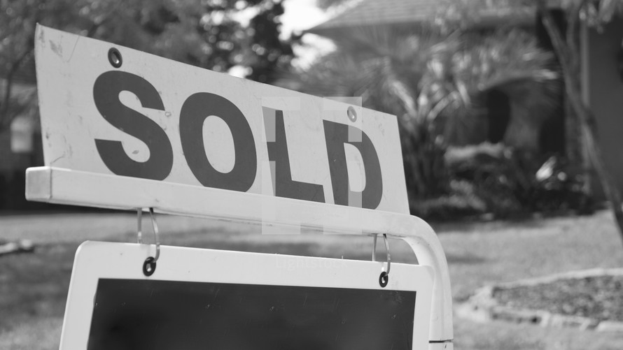 real estate sold sign in front of a house