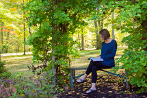 a woman sitting on a bench doing her devotions with a Bible outdoors