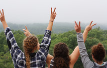friends sitting on a mountaintop giving peace signs