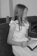 a little girl singing from a hymnal in a church pew