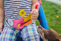 a toddler girl holding a sucker and a dog looking up