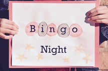 A little girl holding a Bingo Night sign