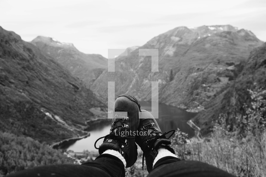 feet in boots hanging over a mountainside
