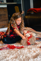 smiling little girl wrapping a Christmas present