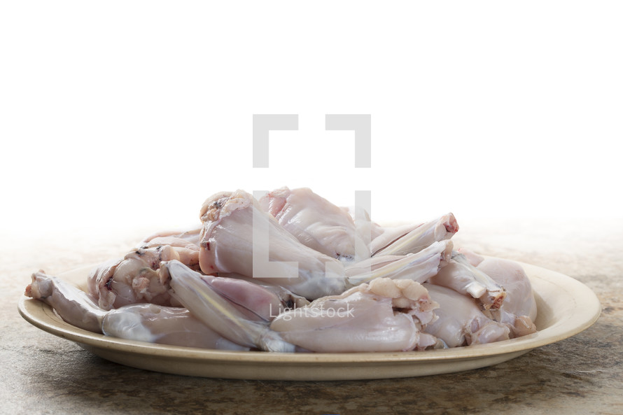 Raw frog legs on a plate