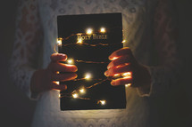 a woman holding a Bible wrapped in fairy lights