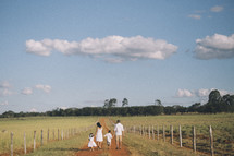 a family walking on dirt road